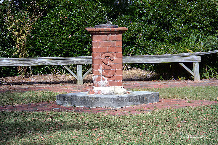 A sun dial stand displays an